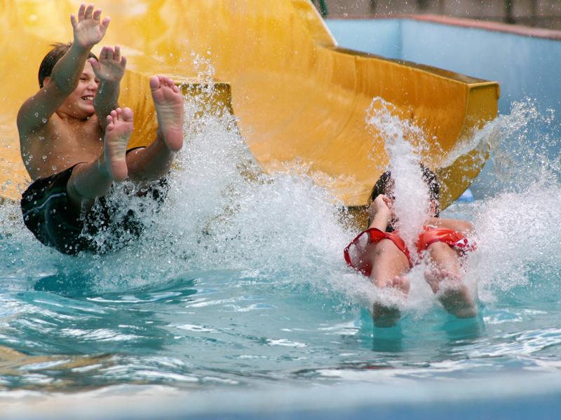 Enfants dans le toboggan d'une piscine - ©Thinkstock